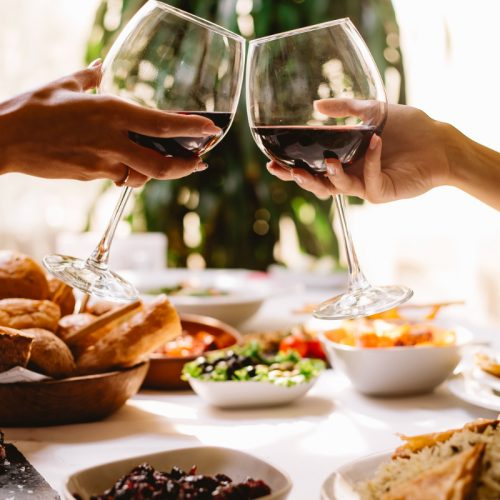 side-view-women-toasting-with-glasses-red-wine-restaurant (1)